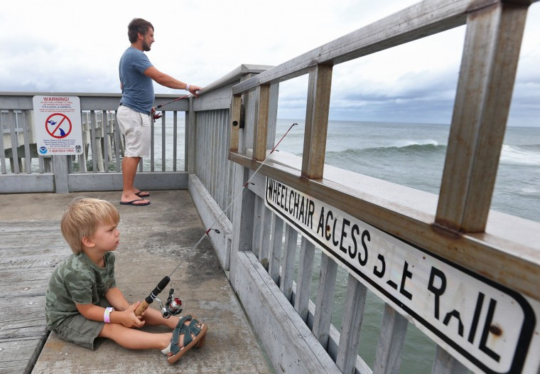 Alex Maksimchuk fishes with his son 3-year-old Aurelius at the County Pier before it was closed in the afternoon in advance of Tropical Storm Hermine, Thursday, Sept. 1, 2016, in Panama City Beach, Fla. Hermine strengthened into a hurricane Thursday and steamed toward Florida's Gulf Coast, where people put up shutters, nailed plywood across store windows and braced for the first hurricane to hit the state in over a decade. (Patti Blake/News Herald via AP)