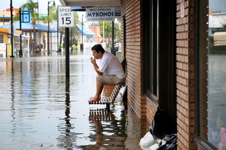Pedro Muacaj rests on higher ground in front of a gift shop along a flooded section of Dodecanese Blvd. in Tarpon Springs, Fla. where he was working. Thursday, Sept. 1, 2016. The street, which typically floods during heavy reins, was filling quickly at high tide as Tropical Storm Hermine strengthened in the Gulf of Mexico, (Douglas R. Clifford/The Tampa Bay Times via AP)