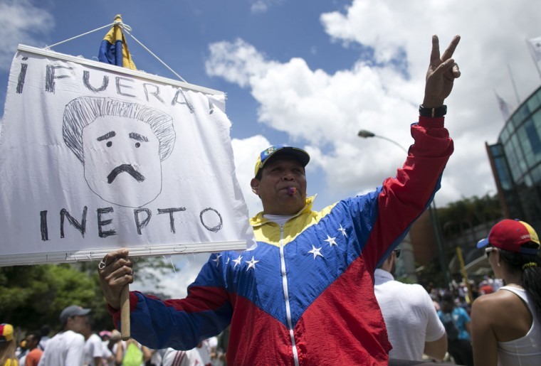"A protester holds a sign with a drawing depicting Venezuela's President Nicolas Maduro and a message that reads in Spanish; ""Get out klutz"" during a march in Caracas, Venezuela, Thursday, Sept. 1, 2016. Venezuela's opposition is vowing to keep up pressure on President Nicolas Maduro after flooding the streets of Caracas with demonstrators Thursday in its biggest show of force in years. Protesters filled dozens of city blocks in what was dubbed the ""taking of Caracas"" to pressure electoral authorities to allow a recall referendum against Maduro this year. (AP Photo/Ariana Cubillos)"