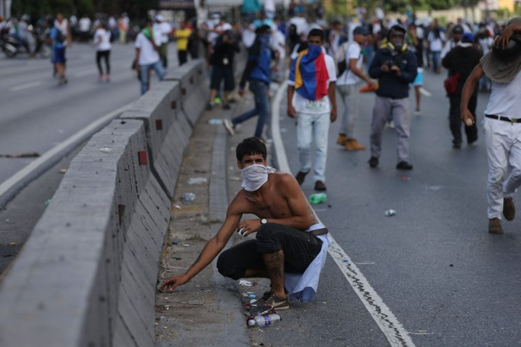 "An anti-government demonstrator picks up a stone during a protest in Caracas, Venezuela, Thursday, Sept. 1, 2016. Venezuela's opposition is vowing to keep up pressure on President Nicolas Maduro after flooding the streets of Caracas with demonstrators Thursday in its biggest show of force in years. Protesters filled dozens of city blocks in what was dubbed the ""taking of Caracas"" to pressure electoral authorities to allow a recall referendum against Maduro this year. (AP Photo/Fernando Llano)"