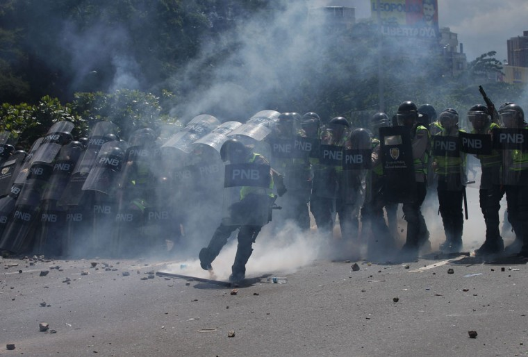 "Police officers aim tear gas at anti-government protesters in Caracas, Venezuela, Thursday, Sept. 1, 2016. Venezuela's opposition is vowing to keep up pressure on President Nicolas Maduro after flooding the streets of Caracas with demonstrators Thursday in its biggest show of force in years. Protesters filled dozens of city blocks in what was dubbed the ""taking of Caracas"" to pressure electoral authorities to allow a recall referendum against Maduro this year. (AP Photo/Fernando Llano)"