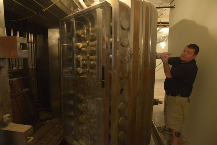 Property manager Tony Sellers closes the vault beneath what was once the Federal Reserve bank in Baltimore. Though the vault is heavy -- Sellers estimates it easily weighs 50 tons, once unlocked, it can be pulled open and closed by a single person. (Christina Tkacik/Baltimore Sun)