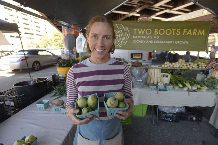 Elisa Lane sells pawpaws at the Sunday Farmers' Market in Baltimore. (Christina Tkacik/Baltimore Sun)