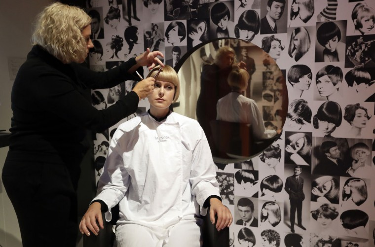 A model receives a signature 1960s style from a Sassoon stylist in a working hair salon during a media opportunity at the 'You Say You Want a Revolution? Records and Rebels 1966-70' exhibition at the V&A museum in London, Wednesday, Sept. 7, 2016. The exhibition explores the era-defining significance and impact of the late 1960s upon life today within a fully immersive and dramatic audiovisual experience. The exhibition opens to the public on Saturday Sept. 10. (AP Photo/Kirsty Wigglesworth)