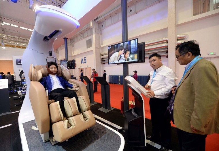 This photo taken on October 20, 2016 shows a visitor trying a robot which can treat cervical spondylosis during the 2016 World Robot Conference in Beijing. More than 2,000 contestants from different countries and regions take part in the conference on October 20 to 25. (STR/AFP/Getty Images)