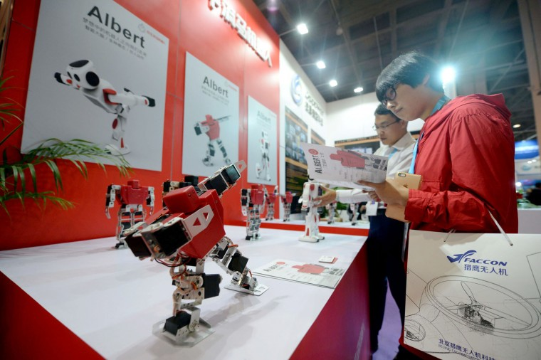 This photo taken on October 20, 2016 shows a visitor reading the instruction book of a smart robot during the 2016 World Robot Conference in Beijing. More than 2,000 contestants from different countries and regions take part in the conference on October 20 to 25. (STR/AFP/Getty Images)