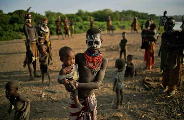 "Members of the Karo tribe pose in front of the Omo river in Ethiopia's southern Omo Valley region on September 23, 2016. The Karo are a Nilotic ethnic group in Ethiopia famous for their body painting. They are also one of the smallest tribes in the region. The construction of the Gibe III dam, the third largest hydroelectric plant in Africa, and large areas of very ""thirsty"" cotton and sugar plantations and factories along the Omo river are impacting heavily on the lives of tribes living in the Omo Valley who depend on the river for their survival and way of life. Human rights groups fear for the future of the tribes if they are forced to scatter, give up traditional ways through loss of land or ability to keep cattle as globalisation and development increases. (AFP PHOTO / CARL DE SOUZA)"