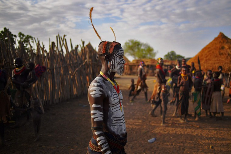 "Members of the Karo tribe pose in Ethiopia's southern Omo Valley region on September 23, 2016. The Karo are a Nilotic ethnic group in Ethiopia famous for their body painting. They are also one of the smallest tribes in the region. The construction of the Gibe III dam, the third largest hydroelectric plant in Africa, and large areas of very ""thirsty"" cotton and sugar plantations and factories along the Omo river are impacting heavily on the lives of tribes living in the Omo Valley who depend on the river for their survival and way of life. Human rights groups fear for the future of the tribes if they are forced to scatter, give up traditional ways through loss of land or ability to keep cattle as globalisation and development increases. (AFP PHOTO / CARL DE SOUZA)"