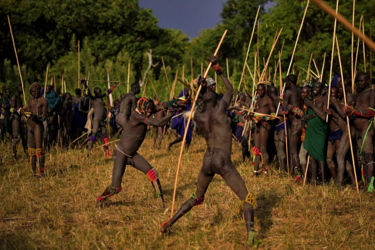 "Men from the Suri tribe take part in a ""Donga"" or stick fight in Ethiopia's southern Omo Valley region near Kibbish on September 24, 2016. Traditionally the fight is a way to impress women and find a wife. The fights are brutal and sometimes result in death. The combatants fight with little or no clothing and sometimes no protection at all. The Suri are a pastoralist Nilotic ethnic group in Ethiopia. The construction of the Gibe III dam, the third largest hydroelectric plant in Africa, and large areas of very ""thirsty"" cotton and sugar plantations and factories along the Omo river are impacting heavily on the lives of tribes living in the Omo Valley who depend on the river for their survival and way of life. Human rights groups fear for the future of the tribes if they are forced to scatter, give up traditional ways through loss of land or ability to keep cattle as globalisation and development increases. (AFP PHOTO / CARL DE SOUZA)"