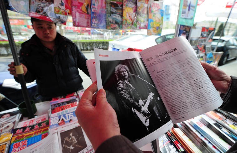 FILE - This file photo taken on April 6, 2011 shows a customer browsing through up a copy of a magazine with an image of Bob Dylan performing at a newsstand in Beijing on April 6, 2011 as the US music legend kicked off a series of first-ever shows in China. US songwriter Bob Dylan won the Nobel Literature Prize on October 13, 2016, the first songwriter to win the prestigious award and an announcement that surprised prize watchers. (Frederic J. Brown/AFP/Getty Images)