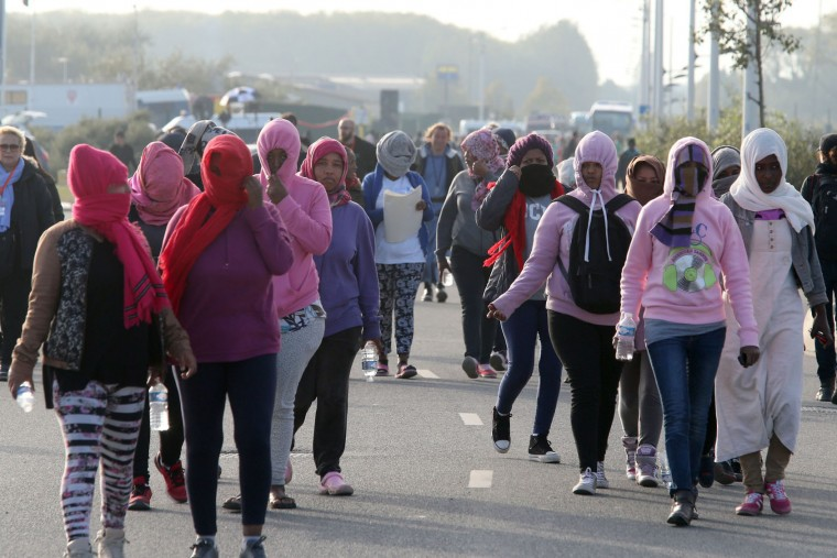 "Migrant women arrive at an official meeting point set by French authorities during the full evacuation of the Calais ""Jungle"" camp, in Calais, northern France, on October 25, 2016. Workers escorted by scores of French police officers moved into the ""Jungle"" in Calais on October 25, demolishing shacks and tents emptied of migrants being bussed to shelters around France. The workers used electric saws to take down wooden shelters and earth-moving equipment to carry debris away from the sprawling camp that people have used for years as a launchpad for attempts to reach Britain. (François Nascimbeni/AFP/Getty Images)"