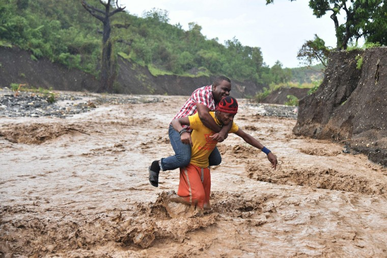 A man is carried across the river La Digue in Petit Goave where the bridge collapsed during the rains of the Hurricane Matthew, southwest of Port-au-Prince, October 5, 2016. Haiti and the eastern tip of Cuba -- blasted by Matthew on October 4, 2016 -- began the messy and probably grim task of assessing the storm's toll. Matthew hit them as a Category Four hurricane but has since been downgraded to three, on a scale of five, by the US National Hurricane Center. (Hector Retamal/AFP/Getty Images)