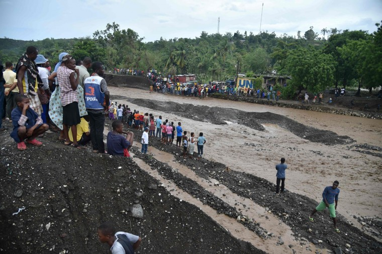 Haitians wait to cross the river La Digue in Petit Goave where the bridge collapsed during the rains of the Hurricane Matthew, southwest of Port-au-Prince, October 5, 2016. Haiti and the eastern tip of Cuba -- blasted by Matthew on October 4, 2016 -- began the messy and probably grim task of assessing the storm's toll. Matthew hit them as a Category Four hurricane but has since been downgraded to three, on a scale of five, by the US National Hurricane Center. (Hector Retamal/AFP/Getty Images)