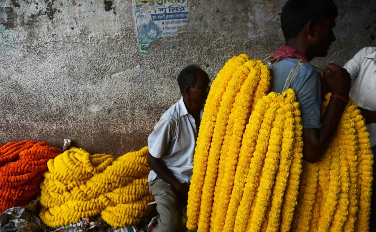 Indian flower vendors and farmers showcase flowers to attract puja organisers for Durga Puja, at a wholesale flower market in Kolkata on October 6, 2016. The five-day Durga Puja festival, which commemorates the slaying of the demon king Mahishasur by the goddess Durga and marks the triumph of good over evil, begins on October 7. (DIBYANGSHU SARKAR/AFP/Getty Images)