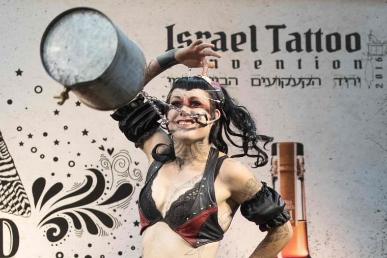 "An artist from ""the Squidling Brothers Circus Sideshow"" performs on stage during the 4th Israel Tattoo Convention in the Israeli coastal city of Tel Aviv, on October 7, 2016. / (AFP Photo/Jack Guez)"