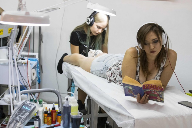 A woman reads as she receives a tattoo on her calf during the 4th Israel Tattoo Convention in the Israeli coastal city of Tel Aviv, on October 7, 2016. / (AFP Photo/Jack Guez)