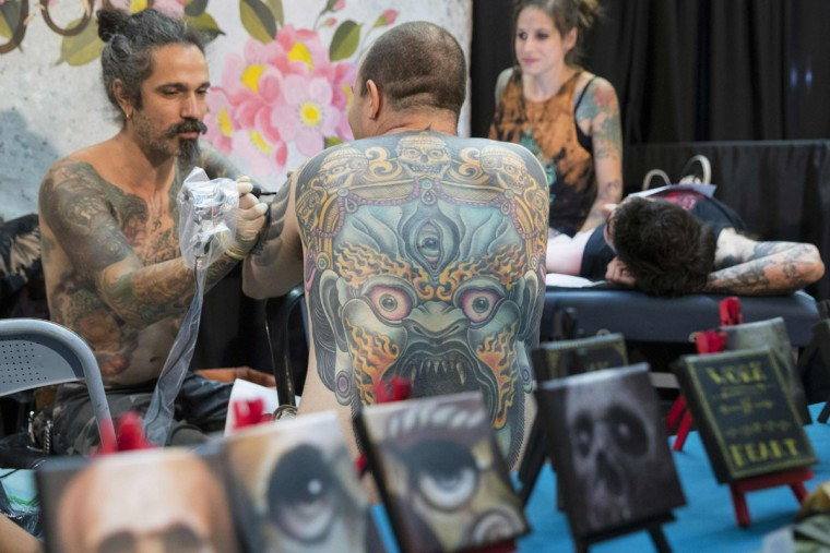 A man receives a tattoo on his arm during the 4th Israel Tattoo Convention in the Israeli coastal city of Tel Aviv, on October 7, 2016. / (AFP Photo/Jack Guez)