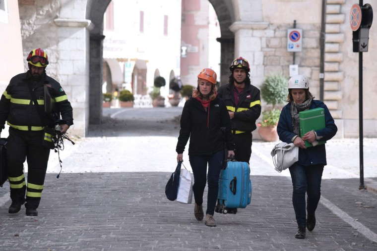 Firefighters help residents to recover their personal belongings from damaged houses in Visso, central Italy, a day after twin earthquakes rocked the area, on October 27, 2016. Two months after a quake left nearly 300 dead in the country's tremor-prone central spine, two powerful shocks ripped through the mountainous, sparsely-populated region on Wednesday evening. Despite numerous building collapses, no deaths had been reported by midday, more than 17 hours after the first of the 5.5 and 6.1 magnitude tremors. (Tiziana Fabi/AFP/Getty Images)
