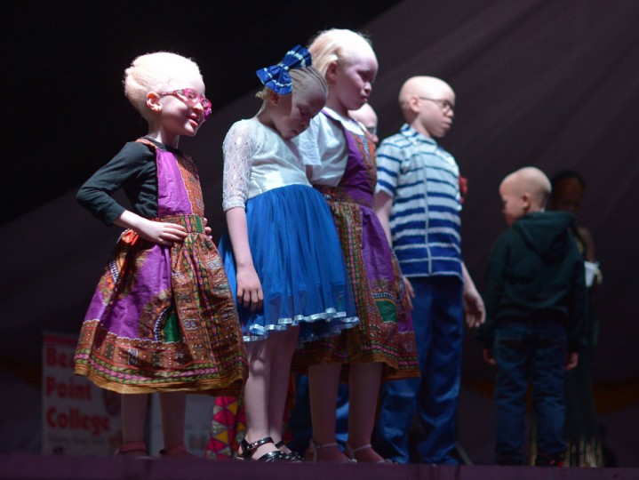 Children stand on stage during a pageant hosted by the Albinism Society of Kenya in Nairobi on October 21, 2016. In many parts of Africa albinos are stigmatized or hunted for their body parts, but for one night in Kenya those with the condition took to the catwalk to show off their unique beauty. Billed by organizers as the first pageant of its kind, young albino men and women competed for the title of Miss and Mr Albinism Kenya. (AFP PHOTO / TONY KARUMBA)