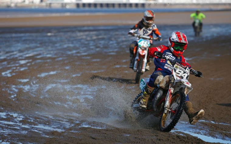 Junior riders round a bend during the Youth 85BW/85SW Race at the 2016 HydroGarden Weston Beach Race in Weston-super-Mare, south west England, on October 9, 2016. Beach racing is an offshoot of enduro and motocross racing. Riders on solo motorcycles and quad bikes compete on a course marked out on a beach, with man-made jumps and sand dunes being constructed to make the course tougher. (ADRIAN DENNIS/AFP/Getty Images)
