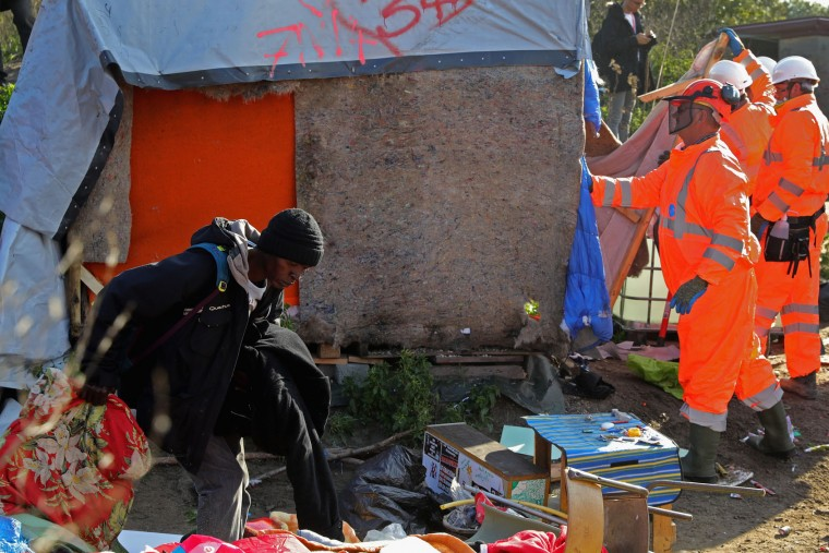 A migrant retrieves his belongings as authorities start to demolish the notorius Jungle camp site on October 25, 2016 in Calais, France. Many migrants have left by coach to be reloctated at centres across France as Police and officials in France begin to clear the 'Jungle' migrant camp in Calais. Some 7,000 people are estimated to be living in the camp in squalid conditions. (Photo by Christopher Furlong/Getty Images)
