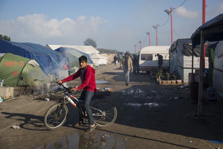 A young migrant is pictured on his bike in the Jungle migrant camp before authorities demolish the site on October 25, 2016 in Calais, France. Many migrants have left by coach to be relocated at centres across France as Police and officials in France begin to clear the 'Jungle' migrant camp in Calais. Some 7,000 people are estimated to be living in the camp in squalid conditions. (Photo by Jack Taylor/Getty Images)