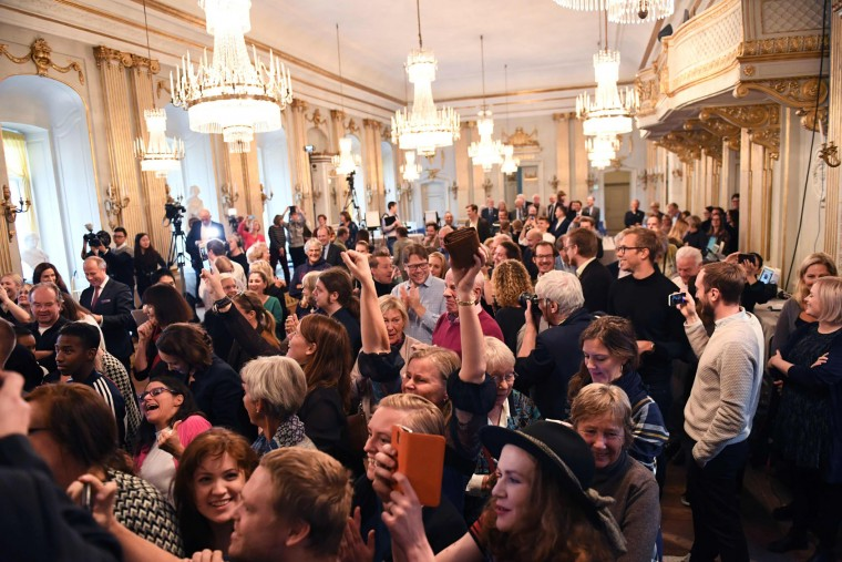 The audience reacts as Permanent Secretary of the Swedish Academy Sara Danius announces that Bob Dylan is awarded the 2016 Nobel Prize in Literature during a presser at the Old Stockholm Stock Exchange Building in Stockholm, on October 13, 2016. (TT News Agency/Jonas Ekstromer/AFP/Getty Images)