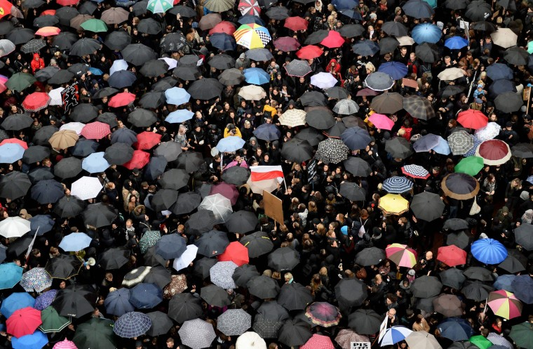 "People protest during a nationwide strike and demonstration against a legislative proposal for a total ban of abortion on October 3, 2016 in Warsaw. Thousands of women dressed in black protested across Poland in the ""Women strike"" campaign against a proposed near-total abortion ban in the devoutly Catholic country where legislation is already among the most restrictive in Europe. (Janek Skarzynski/AFP/Getty Images)"