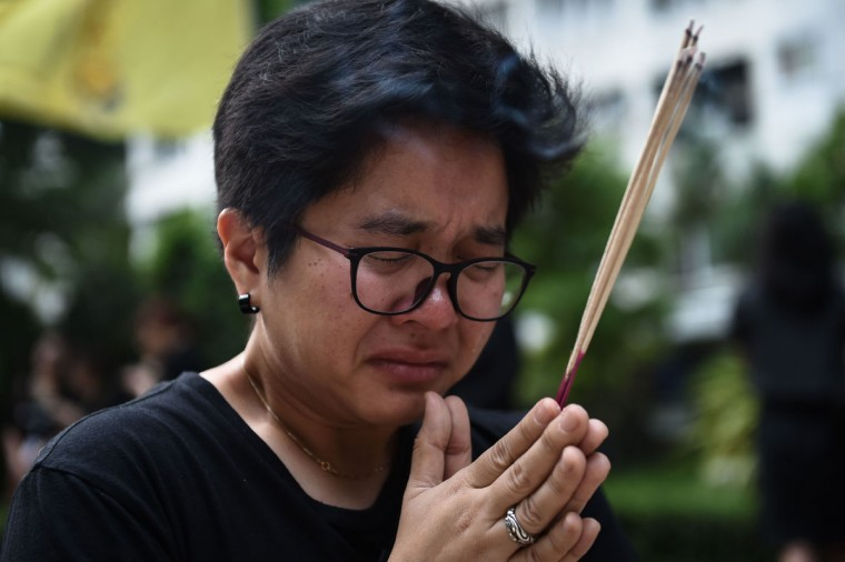 A mourner prays for the late Thai King Bhumibol Adulyadej inside Siriraj Hospital in Bangkok on October 14, 2016. Bhumibol, the world's longest-reigning monarch, passed away aged 88 on October 13, 2016 after years of ill health, removing a stabilising father figure from a country where political tensions remain two years after a military coup / (AFP Photo/Lillian Suwanrumpha)