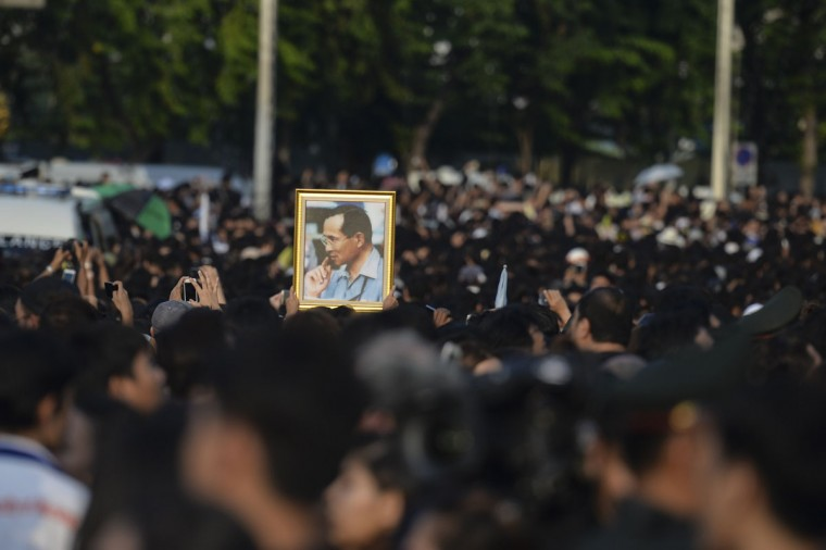 A man holds an image of the late Thai King after the procession of Thai King Bhumibol Adulyadej's body to his palace in Bangkok on October 14, 2016. Bhumibol, the world's longest-reigning monarch, passed away aged 88 on October 13, 2016 after years of ill health, removing a stabilising father figure from a country where political tensions remain two years after a military coup. / (AFP Photo/Munir Zamanmunir uz zaman)