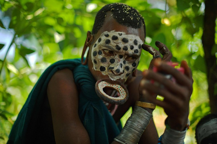"A woman from the Suri tribe wearing a lip plate paints her face in Ethiopia's southern Omo Valley region near Kibbish on September 25, 2016. The Suri are a pastoralist Nilotic ethnic group in Ethiopia. The construction of the Gibe III dam, the third largest hydroelectric plant in Africa, and large areas of very ""thirsty"" cotton and sugar plantations and factories along the Omo river are impacting heavily on the lives of tribes living in the Omo Valley who depend on the river for their survival and way of life. Human rights groups fear for the future of the tribes if they are forced to scatter, give up traditional ways through loss of land or ability to keep cattle as globalisation and development increases. (AFP PHOTO / CARL DE SOUZA)"