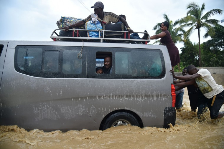People try to cross the overflowing La Rouyonne river in the commune of Leogane, south of Port-au-Prince, October 5, 2016. Haiti and the eastern tip of Cuba -- blasted by Matthew on October 4, 2016 -- began the messy and probably grim task of assessing the storm's toll. Matthew hit them as a Category Four hurricane but has since been downgraded to three, on a scale of five, by the US National Hurricane Center. (Hector Retamal/AFP/Getty Images)