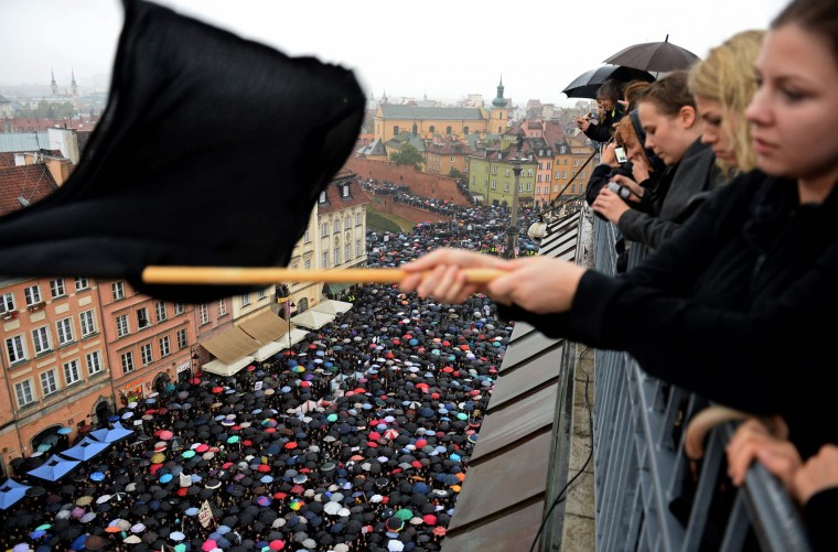 "A girl waves a black flag as people take part in a nationwide strike and demonstration to protest against a legislative proposal for a total ban of abortion on October 3, 2016 in Warsaw. Thousands of women dressed in black protested across Poland in the ""Women strike"" campaign against a proposed near-total abortion ban in the devoutly Catholic country where legislation is already among the most restrictive in Europe. (Janek Skarzynski/AFP/Getty Images)"