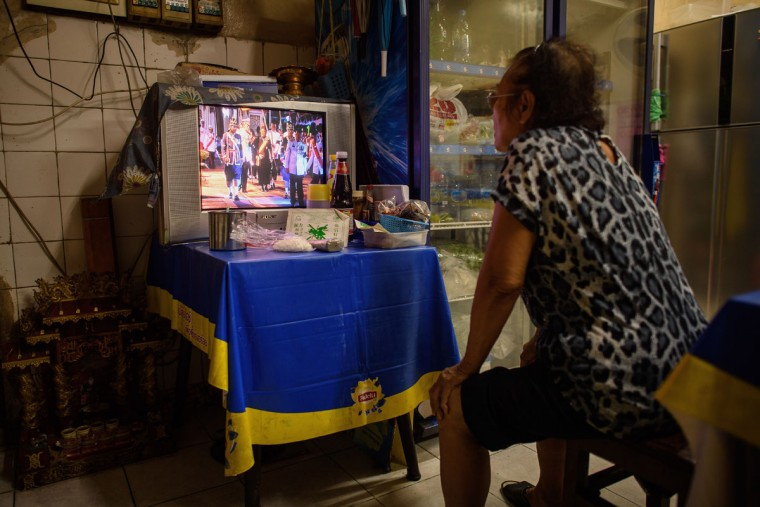 A woman watches a televised broadcast of the ceremonies taking place inside the Grand Palace on October 14, 2016 following the death of King Bhumibol Adulyadej in Bangkok, Thailand. Thailand's King Bhumibol Adulyadej, the world's longest-reigning monarch, died at the age of 88 in Bangkok's Siriraj Hospital on Thursday after his 70-year reign. Prime Minister Prayut Chan-ocha made a statement Thailand would hold a one-year mourning period as the Crown Prince Maha Vajiralongkorn confirmed that he would perform his duty as heir to the throne. (Photo by Leon Neal/Getty Images)