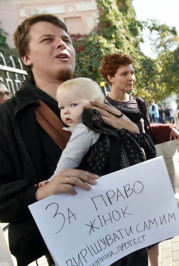 "A Ukrainian activist shouts slogans as he holds his baby and a placard reading ""I am for the right of women to decide for themselves"" during a rally at the Polish embassy in Kiev on October 3, 2016. The activists relly to support thousands of Polish women are expected to go on strike across Poland in protesting against a new law that will ban abortion in the country. (Sergei Supinsky/AFP/Getty Images)"