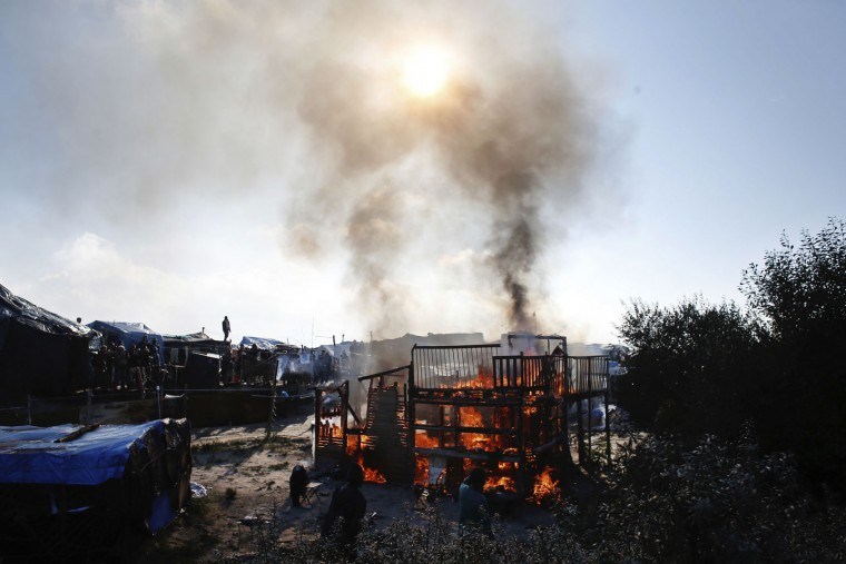 "A man stands on the rooftop as a wooden house burns in the makeshift migrant camp known as ""the jungle"" near Calais, northern France, Tuesday, Oct. 25, 2016. Crews have started dismantling the migrant camp in France after the process to clear the camp began in earnest on Monday. (AP Photo/Thibault Camus)"