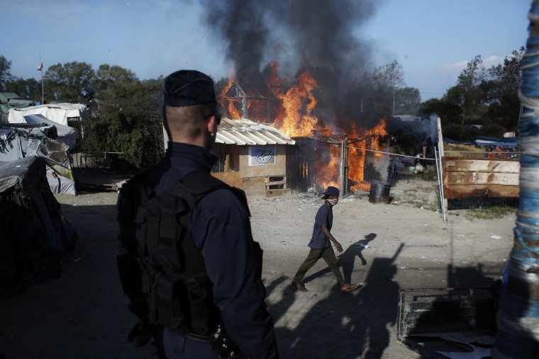 "A man walks past a burning wooden house in the makeshift migrant camp known as ""the jungle"" near Calais, northern France, Tuesday, Oct. 25, 2016. Crews have started dismantling the migrant camp in France after the process to clear the camp began in earnest on Monday. (AP Photo/Thibault Camus)"