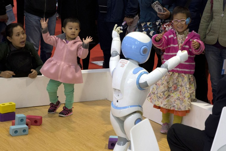 Children dance with a companion robot displayed at the World Robot Conference held in Beijing, China, Friday, Oct. 21, 2016. The conference showcased China's burgeoning robot industry as the nation seeks to increase the use of robots in its manufacturing and service industries. (AP Photo/Ng Han Guan)