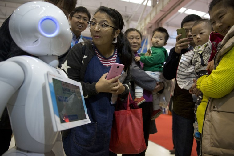 Pepper, a companion robot from e-commerce giant Alibaba, attracts visitors during the World Robot Conference in Beijing, China, Friday, Oct. 21, 2016. The conference showcased China's burgeoning robot industry as the nation seeks to increase the use of robots in its manufacturing and service industries. (AP Photo/Ng Han Guan)