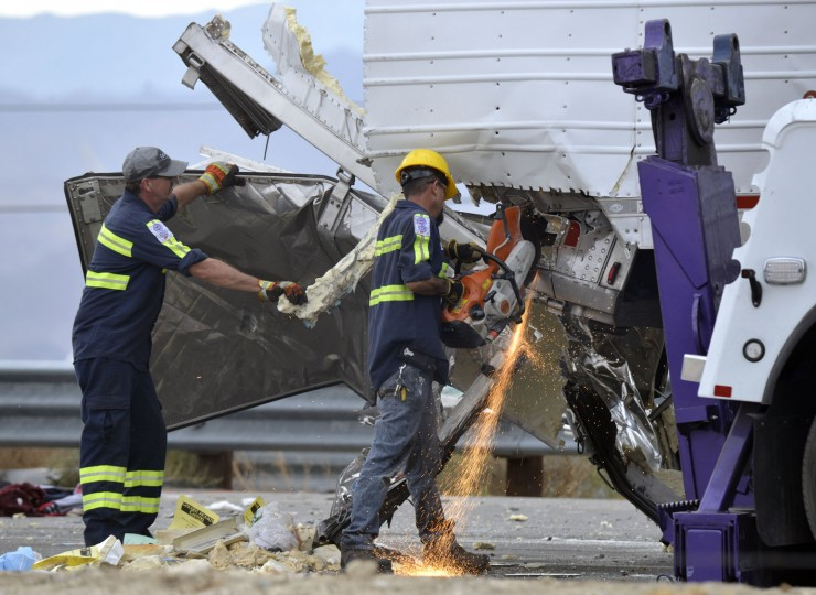 Workers remove wreckage from a semi-truck that crashed with a tour bus on Interstate 10, west of the Indian Canyon Drive off-ramp, in Desert Hot Springs, near Palm Springs, Calif., Sunday, Oct. 23, 2016. A tour bus and the semi-truck crashed on the highway in Southern California early Sunday, killing at least a dozen of people and injuring at least 30 others, some critically, the California Highway Patrol said. (AP Photo/Rodrigo Pena)