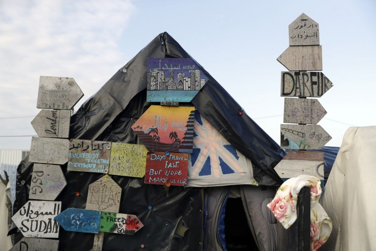 "Outside view of a tent used by migrants and decorated with direction road signs as crews start to demolish shelters in the makeshift migrant camp known as ""the jungle"" near Calais, northern France, Tuesday, Oct. 25, 2016. Crews in hard hats and orange jumpsuits on Tuesday started dismantling a makeshift camp in France that has become a symbol of Europe's migrant crisis while thousands of people remained there waiting to be relocated. (AP Photo/Matt Dunham)"