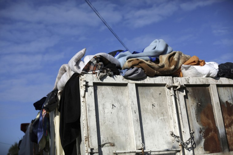 "Belongings of migrants are carried in a truck as crews start to demolish shelters in the makeshift migrant camp known as ""the jungle"" near Calais, northern France, Tuesday, Oct. 25, 2016. Crews have started dismantling the squalid migrant camp in France after the process to clear the camp began in earnest on Monday. (AP Photo/Thibault Camus)"
