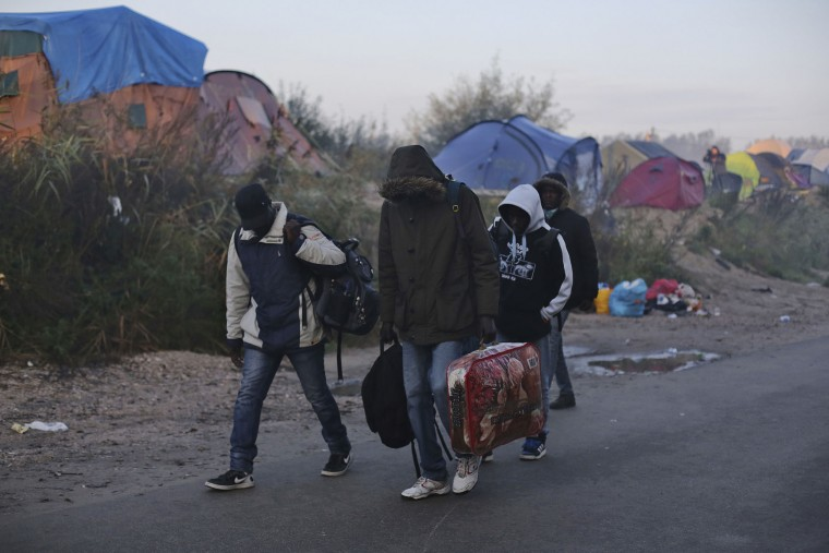 "Migrants carry their belongings as they leave a makeshift camp known as ""the jungle"" to register at a processing center, near Calais, northern France, Tuesday, Oct. 25, 2016. France began the mass evacuation Monday of the makeshift migrant camp, a mammoth project to erase the humanitarian blight on its northern border, where thousands fleeing war or poverty have lived in squalor, most hoping to sneak into Britain. (AP Photo/Thibault Camus)"
