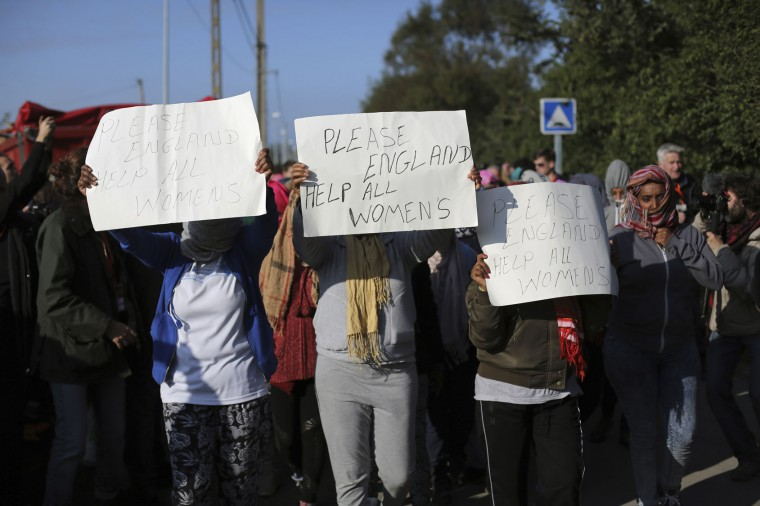 "Women hod placards as they demonstrate in the makeshift migrant camp known as ""the jungle"" near Calais, northern France, Tuesday, Oct. 25, 2016. Crews have started dismantling the migrant camp in France after the process to clear the camp began in earnest on Monday. (AP Photo/Thibault Camus)"