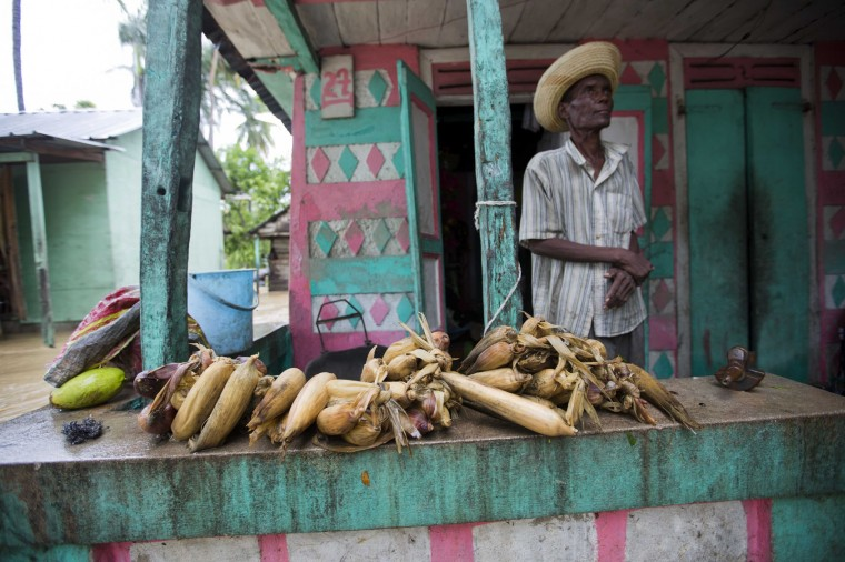 Farmer Antoine Louis, 72, stands on his porch before cobs of corn he was able to salvage after the passing of Hurricane Matthew, in Leogane, Haiti, Wednesday, Oct. 5, 2016. Rescue workers in Haiti struggled to reach cutoff towns and learn the full extent of the death and destruction caused by Hurricane Matthew as the storm began battering the Bahamas on Wednesday and triggered large-scale evacuations along the U.S. East Coast. (AP Photo/Dieu Nalio Chery)