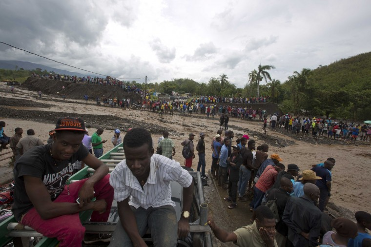 People watch from both sides of the La Digue river as water roars past where the Petit Goave bridge once stood, destroyed by Hurricane Matthew, in Petit Goave, Haiti, Wednesday, Oct. 5, 2016. Rescue workers in Haiti struggled to reach cutoff towns and learn the full extent of the death and destruction caused by Hurricane Matthew as the storm began battering the Bahamas on Wednesday and triggered large-scale evacuations along the U.S. East Coast. (AP Photo/Dieu Nalio Chery)