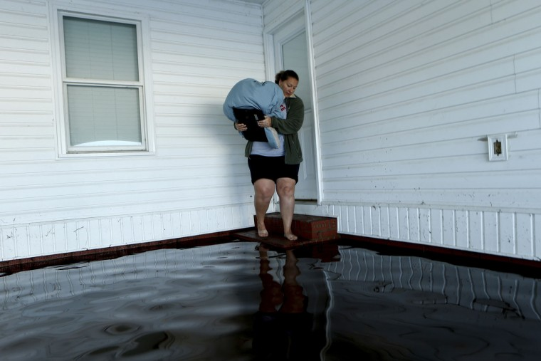 With her home surrounded by floodwaters associated with Hurricane Matthew, Janet Meier prepares to step back into the water in her carport after retrieving a warm blanket and her laptop computer on Thursday, Oct. 13, 2016, in Lumberton, N.C. About 1,200 Lumberton residents had to be evacuated by boat and plucked from their roofs by helicopters as the river crested. (AP Photo/Brian Blanco)