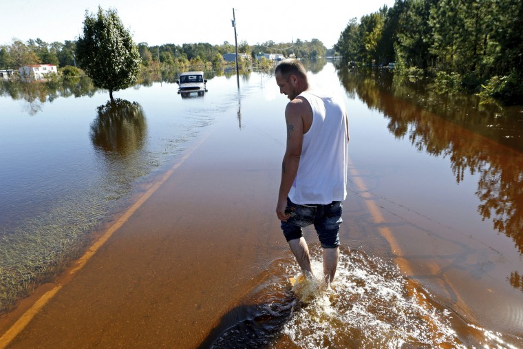 Elmer McDonald makes his way along the flooded street to his home as he returns to his mobile home for the first time to inspect damage caused by floodwaters associated with Hurricane Matthew on Thursday, Oct. 13, 2016, in Lumberton, N.C. About 1,200 Lumberton residents had to be evacuated by boat and plucked from their roofs by helicopters as the river crested; McDonald was one of thousands who evacuated. (AP Photo/Brian Blanco)