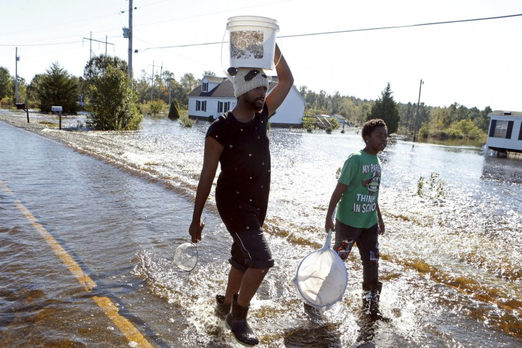 Cedric Blackmon, left, entertains neighbor Jaywuan McMillian, 13, by catching small fish and crawfish on a road covered in floodwater associated with Hurricane Matthew on Thursday, Oct. 13, 2016, in Lumberton, N.C. About 1,200 Lumberton residents had to be evacuated by boat and plucked from their roofs by helicopters as the river crested. (AP Photo/Brian Blanco)