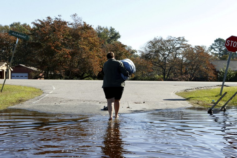 Janet Meier makes her way out of the floodwaters associated with Hurricane Matthew surrounding her home after retrieving a warm blanket and her laptop computer from her home on Thursday, Oct. 13, 2016, in Lumberton, N.C. About 1,200 Lumberton residents had to be evacuated by boat and plucked from their roofs by helicopters as the river crested. (AP Photo/Brian Blanco)